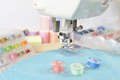 Machine à coudre et petits pains de fil, ciseaux, tissu et a colorés Photo libre de droits