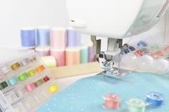 Machine à coudre et petits pains de fil, ciseaux, tissu et a colorés Images libres de droits