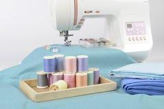 Machine à coudre et petits pains de fil, ciseaux, tissu et a colorés Photographie stock libre de droits