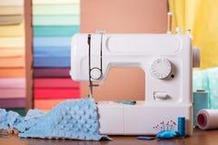 Machine à coudre et tissu dans le travail, approvisionnements de couture sur la table Photos stock