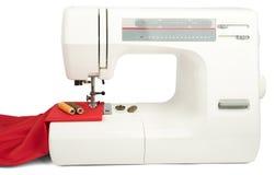 Machine à coudre et tissu rouge d'isolement sur le blanc Photographie stock