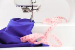 Machine à coudre, textile drapé et centimètre sur un backgro blanc Images stock