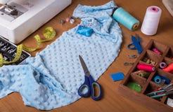 Machine à coudre, tiroir avec des accessoires, morceau de tissu bleu-clair et ciseaux sur le bureau Photographie stock libre de droits