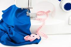 Machine à coudre, tissu drapé et centimètre sur un backgrou blanc Photo libre de droits