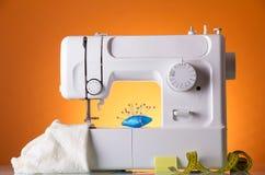Machine à coudre, tissu sous le pied de couture, oreiller avec des aiguilles et centimètre, sur le fond orange Photo libre de droits