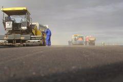 Machine à paver dépistée étendant le trottoir frais d'asphalte sur une piste en tant qu'élément du plan d'expansion d'aéroport in Photographie stock libre de droits