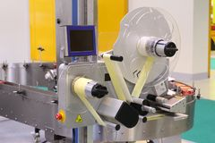 Machine for applying self-adhesive labels. The machine is designed for automatic labeling on a cylindrical container royalty free stock photography