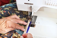 Machine binding a quilt. A quilter guides binding material through the walking foot of a sewing machine Royalty Free Stock Photography