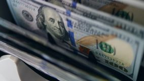 A machine checks authenticity of dollar banknotes, moving them on a line. 4K stock footage