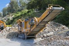 Machine for crushing concrete. Yellow machine for crushing concrete, between work Stock Photo