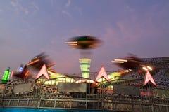 Machine d'amusement dans le parc à thème au crépuscule Photos stock