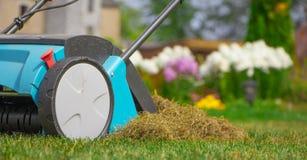 Machine d'Operating Soil Aeration de jardinier sur la pelouse d'herbe photos stock