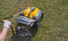 Machine d'Operating Soil Aeration de jardinier sur la pelouse d'herbe photo stock