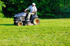 Machine de fauchage professionnelle fonctionnante d'herbe photographie stock libre de droits