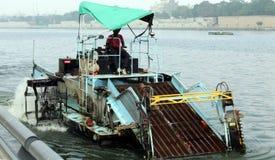 Machine de nettoyage de mauvaise herbe de rivière - bateau de collection de déchets de rivière à la façade d'une rivière de Sabar Photo stock