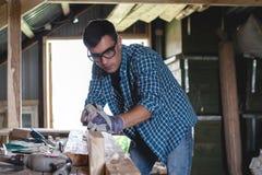 Machine de rabotage en bois de main d'avions de menuisier dans l'atelier à la maison Entrepreneur privé travaillant sur son lieu  photo stock