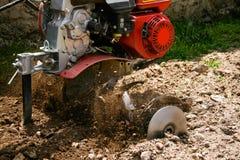 Machine die het land ploegen die stenen en overblijfselensprong maken stock afbeeldingen