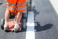 Machine eject and worker on road and traffic sign painting Stock Photos