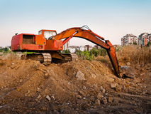 Machine excavating earth near city. Red construction machine excavating earth near city stock photography