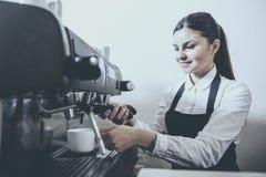 Machine fonctionnante de fabricant de café de barman femelle joyeux dans le café photographie stock