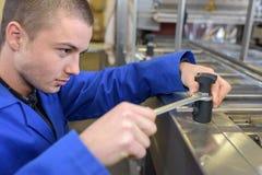 Machine fonctionnante de jeune ouvrier image stock