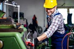 Machine fonctionnante de tour de Turner de travailleur en métal à l'usine de fabrication industrielle photographie stock
