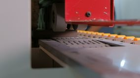 Machine for gluing edges on chipboard parts. Furniture manufacture. Shallow depth of field, selective focus. The mechanism of auto stock video footage