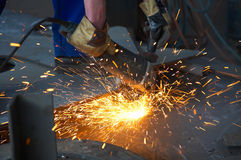 Machine for grinding metal and sparks. Worker holding a machine for grinding metal and sparks spreading Stock Photography