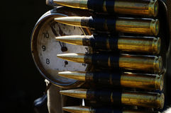 Machine gun ammunition and alarm clock Royalty Free Stock Images