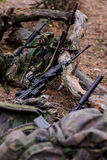 Machine gun and camouflage backpacks in forest. Machine gun,assault rifles and camouflage backpacks in forest stock image