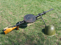 Machine gun and military helmet on grass. Machine gun and military helmet on green grass Stock Photos