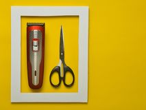 The machine for a hairstyle and scissors in a white frame on a yellow background. Minimalist trend. Copy space.  royalty free stock images