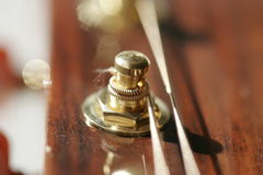 Machine head on guitar. Macro machine head and strings on wooden guitar stock photography