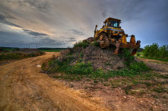 Machine on the hill. Bulldozer parked on a hill in the evening landscape Royalty Free Stock Images