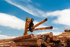 Machine lifts timber onto a stack Royalty Free Stock Photo