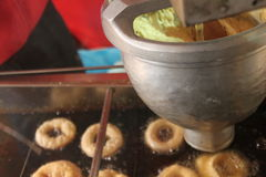 Machine making donuts with sugar and hole. Donut making machine frying with sugar and hole on conveyer belt Royalty Free Stock Photo