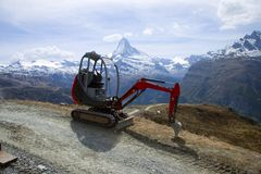 Machine And The Mountain. A Construction Machine in Swiss Apls Stock Photography