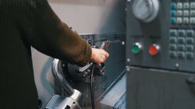 The machine operator flushes the lathe with a liquid. Close up stock video footage