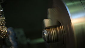 A machine operator removes a brilliant a rotating part with a milling machine with coolant. stock footage