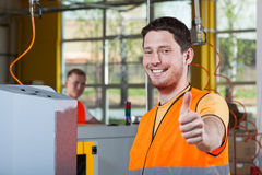 Machine operator showing thumbs up sign. Machine operator in protective vest showing thumbs up sign Royalty Free Stock Photos
