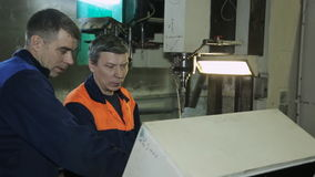 Machine operator shows a colleague a job and adjusts coolant. Drilling on CNC machine you need to install correct flow of coolant. A more experienced employee stock video footage