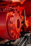 Machine part. Joint of flanges by bolts and nuts red colored. Close-up view stock images