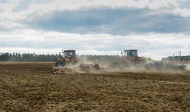 Machine plowing field. A tractor working in a field plowed soil Stock Photos