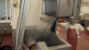 Machine processing of raw meat for production. water is poured into the tank with meat sauce stock footage