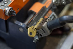Machine production of duplicate metal key. Royalty Free Stock Photography