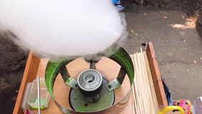 Machine for the production of sweet cotton candy on a stick. Street food. stock video footage