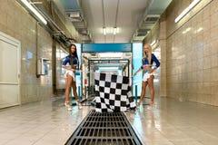 Machine propre de Washington de véhicule, lavage de voiture avec l'éponge et boyau Filles aux longues jambes posant avec les drap Photos libres de droits