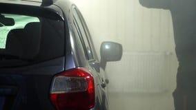 Machine propre de Washington de véhicule, lavage de voiture avec l'éponge et boyau Un travailleur de station de lavage lave une v banque de vidéos