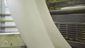 Machine pulls and twists large paper roll in printing house stock video