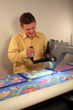 Machine Quilting. A blue flower quilt on a 12' quilting machine Stock Photo